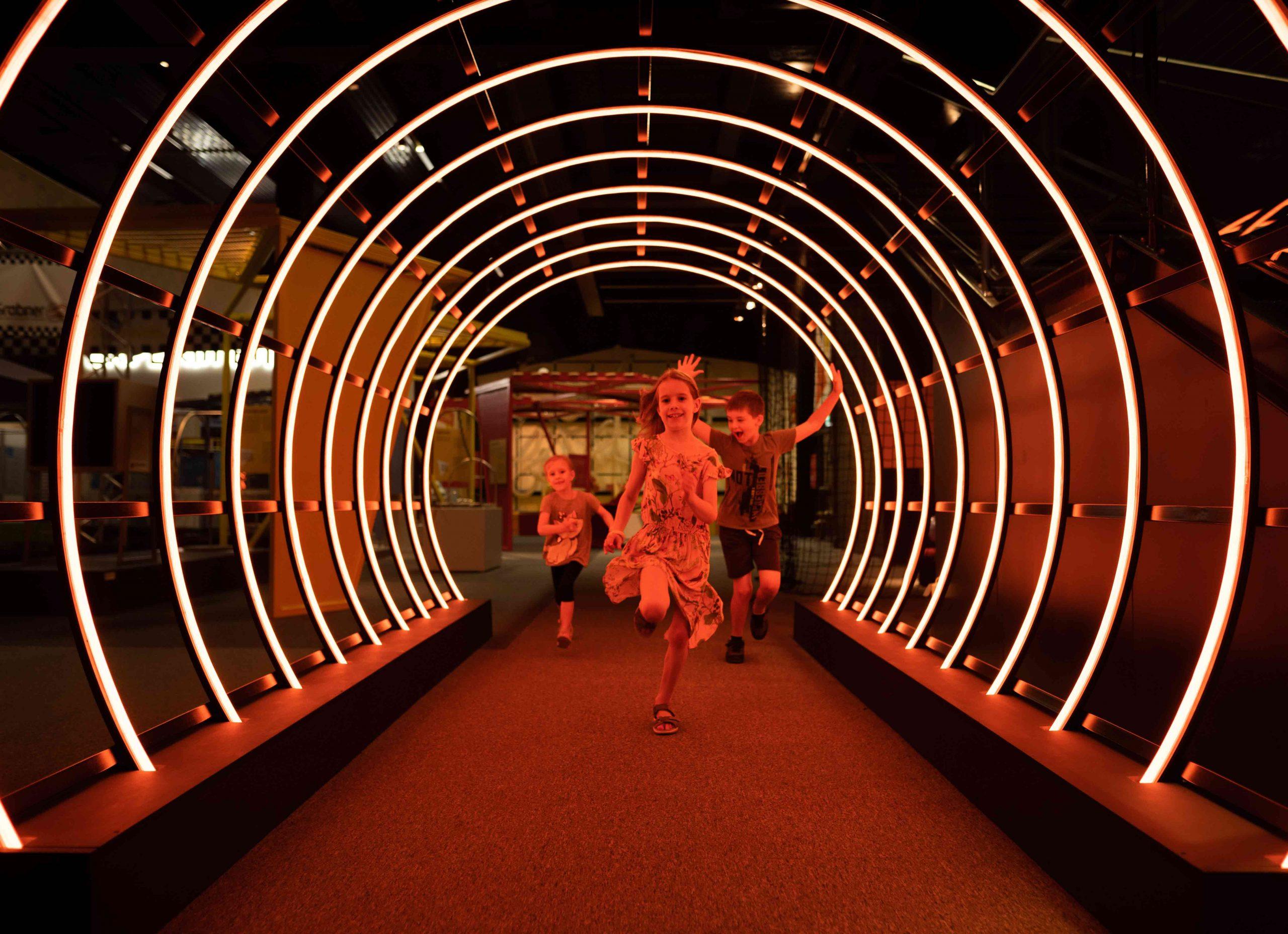 Experimentarium Kinder laufen durch den Lichttunnel